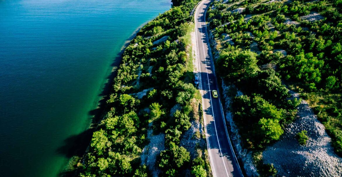 aerial-view-of-road-near-blue-sea-and-green-mounta-SPVWKR9.jpg